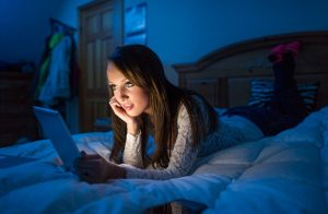 D2P8E3 Teenage girl in the dark lying on a bed working on a tablet computer.